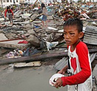 A boy gathers salvageable materials from the ruins of houses after Super Typhoon Haiyan battered Tacloban, Philippines. (CNS/Reuters)