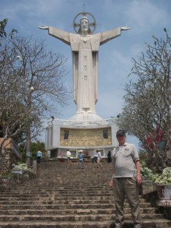Fr. Schineller poses in front of a statue of Jesus.