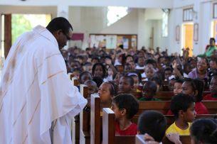 Fr. Rohan Tulloch, SJ, greets children at St. Anne's Church, in Jamaica.